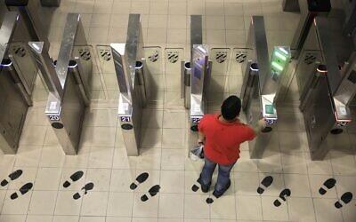 Un Palestinien utilise un portail biométrique alors qu'il entre en Israël au point de passage de Qalandiya à Jérusalem, le 11 juillet 2019. (Sebastian Scheiner/AP)