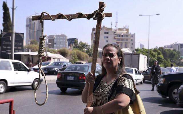 Une ancienne détenue de la prison de Khiam tient une fausse potence lors d'un sit-in près d'un tribunal militaire où un mandat d'arrêt a été délivré contre Amer Fakhoury, libano-américain, qui a avoué avoir travaillé pour Israël pendant son occupation du Liban pendant presque deux décennies, à Beyrouth, Liban, le mardi 17 septembre 2019. (AP Photo/Bilal Hussein)