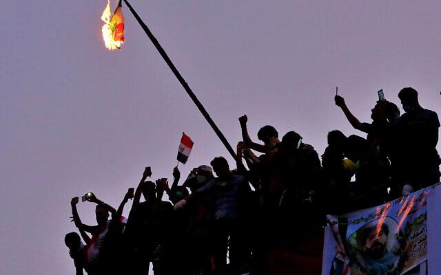 Des manifestants anti-gouvernementaux irakiens brûlent le drapeau iranien lors d'une manifestation à Bagdad, en Irak, le mardi 29 octobre 2019. (Crédit : AP / Hadi Mizban)