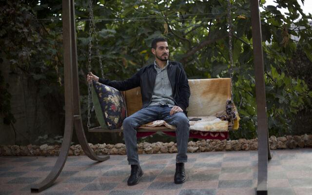 Le Palestinien Karam Qawasmi, qui a été blessé dans le dos par balle par les forces israéliennes lors d'un incident filmé l'an dernier, est assis dans son jardin, à Hébron, en Cisjordanie, le dimanche 10 novembre 2019. (AP Photo/Majdi Mohammed)