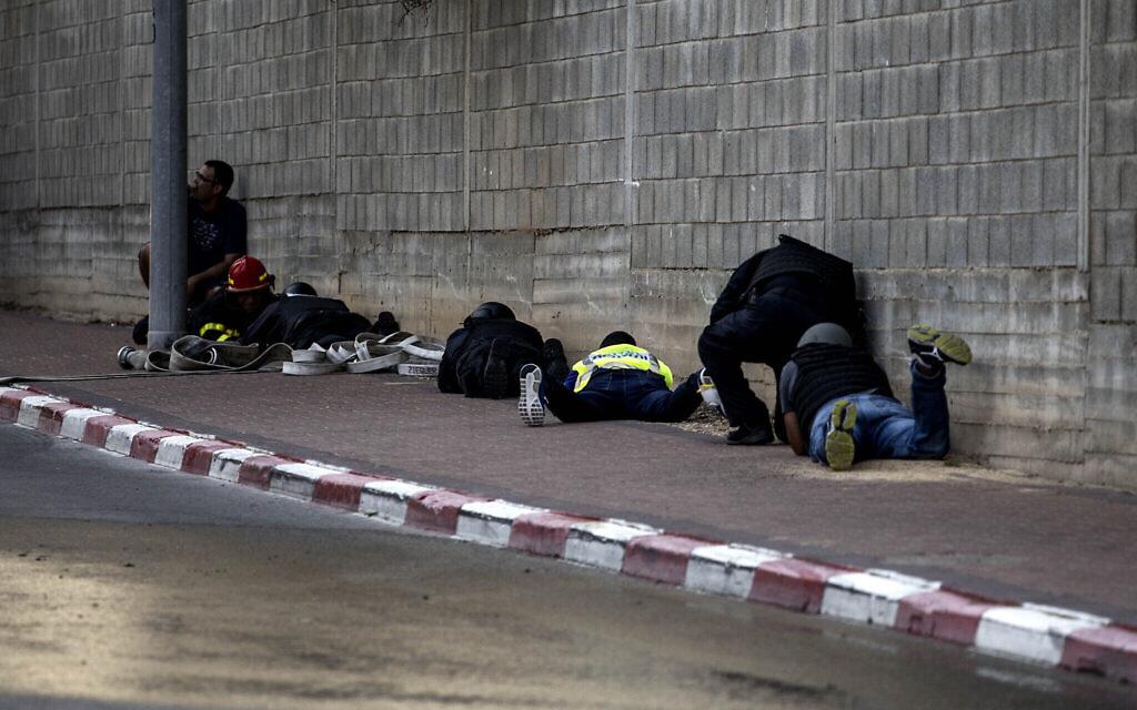 Des Israéliens se protègent au sol durant une sirène d'alarme à la roquette, à Sdérot le 12 novembre 2019. (Crédit : AP Photo/Tsafrir Abayov)