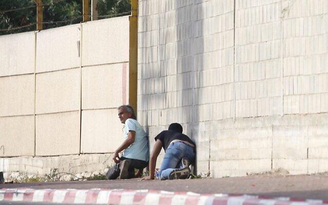 Des gens s'abritent pendant une alerte au raid aérien dans la ville de Sdérot, le 13 novembre 2019 (Crédit : AP Photo/Ariel Schalit)