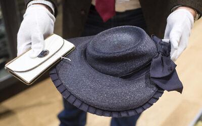 Un employé tient un portefeuille et un chapeau ayant appartenu à Eva Braun, épouse d'Adolf Hitler, avant une vente aux enchères à Grasbrunn, en Allemagne, le mercredi 20 novembre 2019. (Crédit : Matthias Balk / dpa via AP)