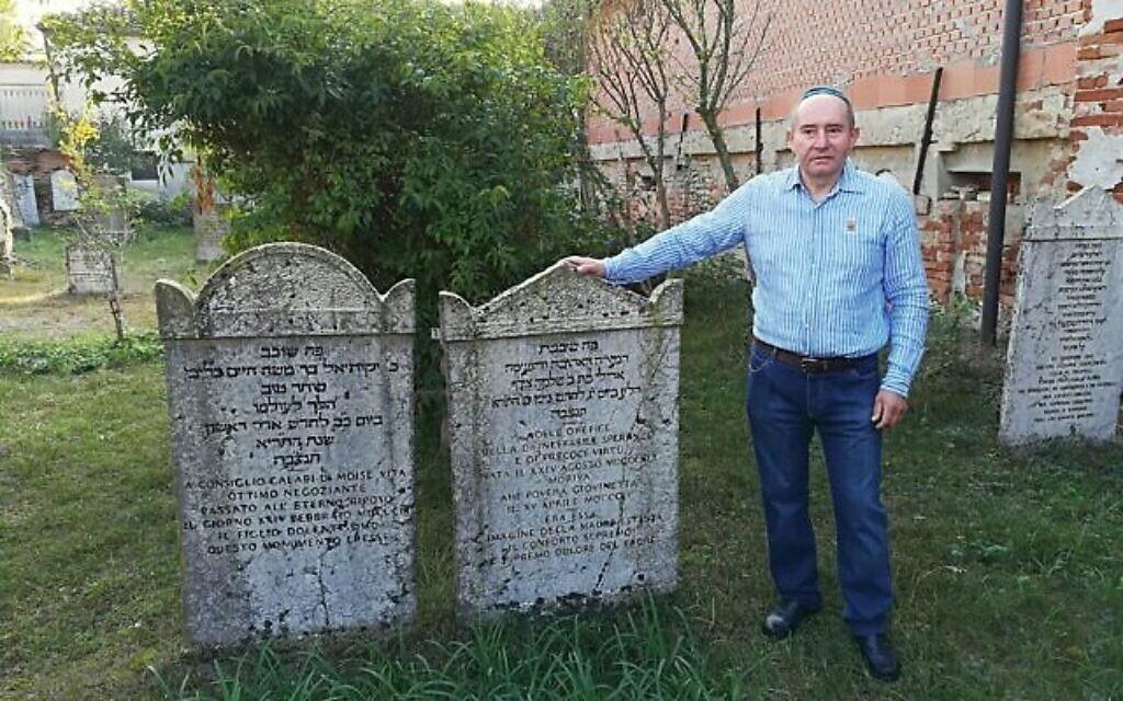Giuseppe Minera près de deux stèles du cimetière juif d'Ostiano, en Italie (Crédit : Giovanni Vigna/ Times of Israel)