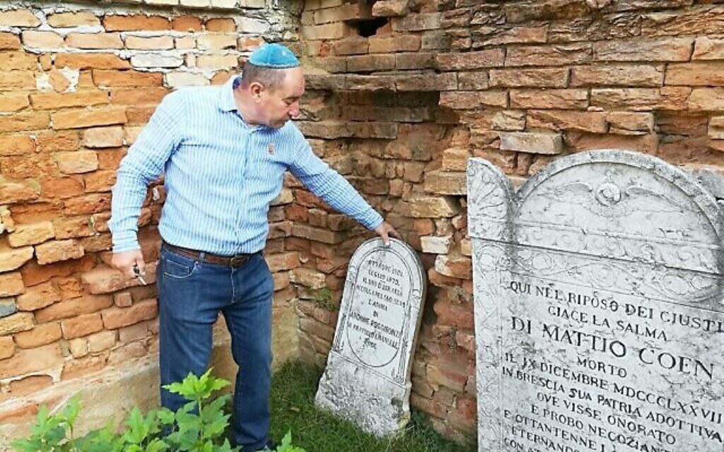 Giuseppe Minera touche une stèle à côté du mur en pierre et en briques délabré du cimetière juif d'Ostiano, en Italie (Crédit : Giovanni Vigna/ Times of Israel)
