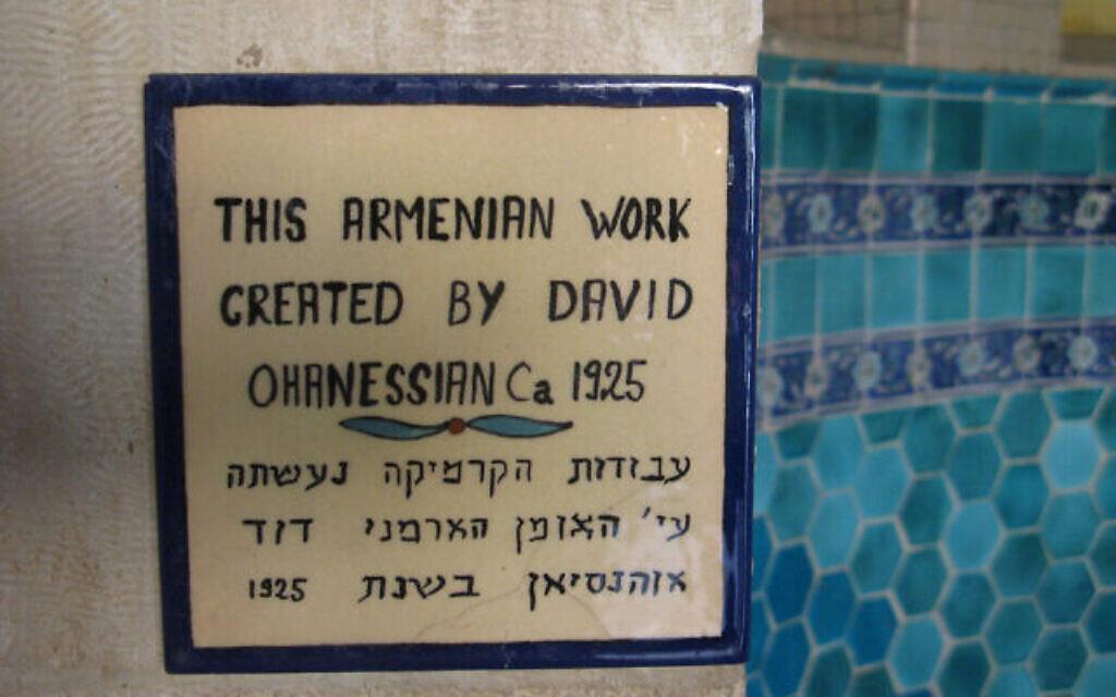 Un panneau en anglais et en hébreu attribue le travail en céramique réalisé à côté au maire-artisan arménien David Ohannessian. (Crédit : Wikimedia commons/CC-SA-3.0/Lantuszka)