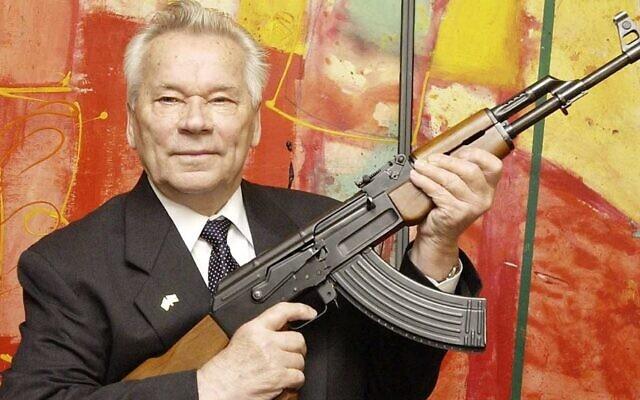 """Le concepteur d'armes russe Mikhail Kalachnikov présente aux médias son fusil d'assaut légendaire lors de l'ouverture de l'exposition """"Kalachnikov - légende et malédiction d'une arme"""" dans un musée de l'armement à Suhl, en Allemagne, le 26 juillet 2002. (AP / Jens Meyer)"""