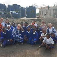 Les étudiants de la faculté d'ingénierie de l'université de Tel Aviv avec un groupe d'enfants de l'école tanzanienne qu'ils ont raccordée à l'eau potable. (Crédit : Amis français de l'université de Tel Aviv)