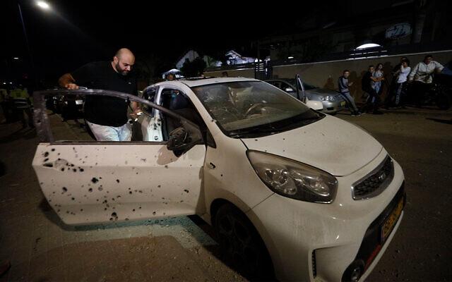 Un homme regarde une voiture endommagée par un éclat d'obus issu d'une roquette tirée de Gaza à Sdérot, en Israël, le 1er novembre 2019 (Crédit : AP Photo/Tsafrir Abayov)