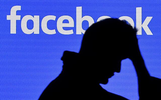 Illustration  un homme devant un écran de Facebook au Gamescom à Cologne, en Allemagne, le 20 août 2019. (Crédit : AP Photo/Martin Meissner)