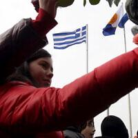Photo d'illustration : Des enfants mettent des fleurs sur un site de commémoration de la Shoah en souvenir des persécutions des Juifs pendant la Seconde guerre mondiale à Thessalonique, en Grèce, le 27 janvier 2013 (Crédit : AP Photo/Nikolas Giakoumidis)