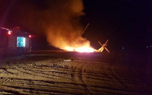 Des pompiers travaillent sur un hélicoptère en feu, près de Rahat dans le désert du Négev, le 26 novembre 2019. (Crédit : sapeurs-pompiers)