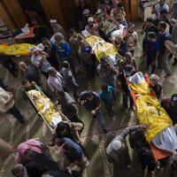 Des Palestiniens endeuillés portent les dépouilles de Rasmi Abu Malhous et de sept membres de sa famille qui ont été tués dans des frappes de missiles israéliens qui ont ciblé leur maison, lors d'un enterrement à la mosquée à Deir al-Balah, au centre de la bande de Gaza, le jeudi 14 novembre 2019.  (AP Photo/Khalil Hamra)