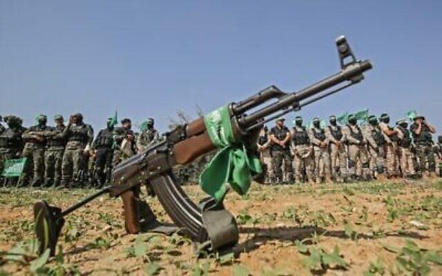 Des combattants des brigades Ezzedine Al-Qassam, aile militaire du groupe terroriste du Hamas, derrière un fusil automatique à Khan Younès, dans le sud de la bande de Gaza, le 11 novembre 2019 (Crédit : Said Khatib/AFP)