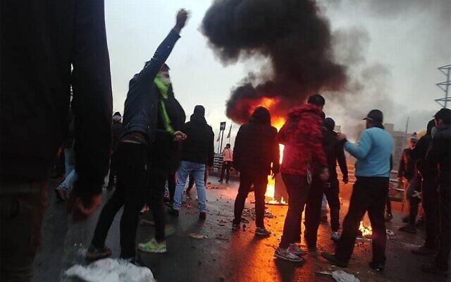 Des manifestants iraniens se rassemblent autour d'un feu lors d'une manifestation contre l'augmentation du prix de l'essence dans la capitale Téhéran, le 16 novembre 2019. (Crédit : AFP)