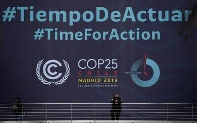"""Un garde de sécurité devant la banderole du sommet COP25 sur le climat """"Time for Action"""", au centre de conférence IFEMA de Madrid, le 30 novembre 2019, où le sommet se tiendra du 2 au 13 décembre 2019. (Crédit : Pierre-Philippe Marcou/AFP)"""