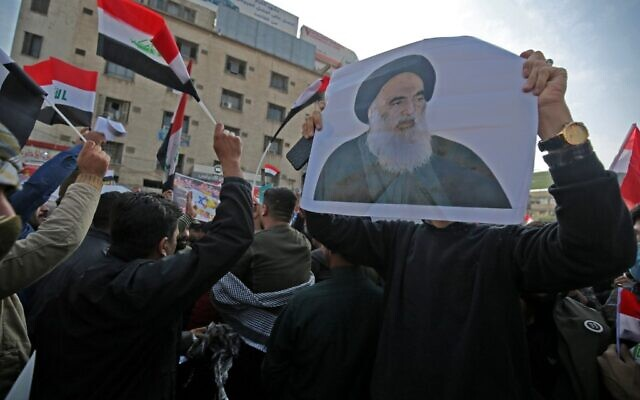 Des partisans irakiens du groupe armé Hashed Al-shaabi tiennent une photo de la plus haute autorité religieuse chiite du pays, l'Ayatollah Ali Sistani, alors qu'ils manifestent sur la place Tahrir de la capitale Baghdad, le 4 décembre 2019.  (Photo par AHMAD AL-RUBAYE / AFP)