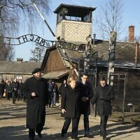La chancelière allemande Angela Merkel accompagnée du Premier ministre Mateusz Morawiecki et le directeur du musée d'Auschwitz-Birkenau Piotr Cywinski, au camp de concentration, le 6 décembre 2019. (Crédit : SKARZYNSKI / AFP)