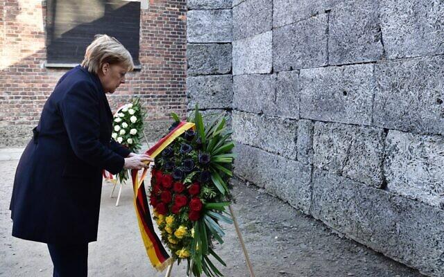 La chancelière allemande Angela Merkel dépose une gerbe de fleurs devant le Mur des noms, à Auschwitz, le 6 décembre 2019. (Crédit : John MACDOUGALL / AFP)