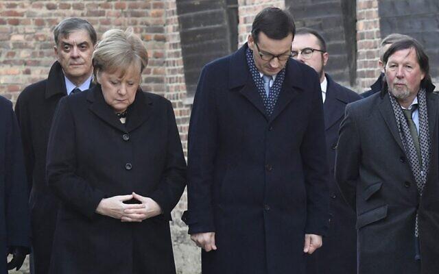 La chancelière allemande Angela Merkel et le premier ministre polonais Mateusz observent une minute de silence devant le Mur des noms, à Auschwitz, le 6 décembre 2019. (Crédit : John MACDOUGALL / AFP)