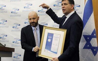 L'homme d'affaires libano-suisse Abdallah Chatila (L), qui a acheté des articles appartenant à Adolf Hitler lors d'une vente aux enchères en Europe pour s'assurer qu'ils ne tombent pas entre les mains de néo-nazis, reçoit de Sam Grundwerg, président mondial de la fondation Keren Hayessod-UIA, un certificat d'appréciation au siège de l'association israélienne de collecte de fonds à Jérusalem, le 8 décembre 2019. (Crédit : AHMAD GHARABLI / AFP)