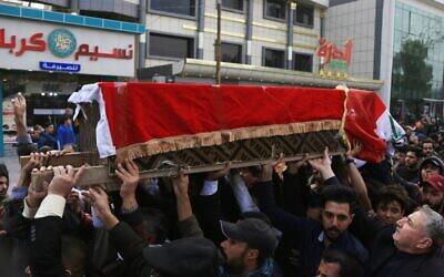 Des Irakiens portent le cercueil d'un éminent militant de la société civile qui a été abattu la nuit précédente alors qu'il rentrait chez lui après des manifestations antigouvernementales, lors de ses funérailles à Karbala, une ville sanctuaire irakienne, le 9 décembre 2019, au sud de la capitale Bagdad.. (Crédit : Mohammed SAWAF / AFP)