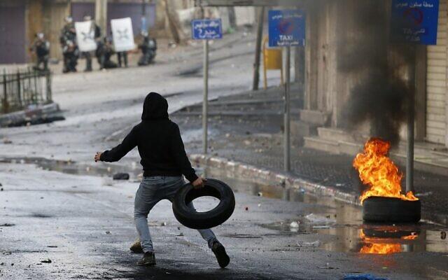 Un manifestant palestinien lance un pneu lors d'affrontements avec les forces de sécurité israéliennes dans la ville de Hébron, au sud de la Cisjordanie, le 9 décembre 2019, au milieu d'une grève générale contre les activités de construction israéliennes. (HAZEM BADER / AFP)