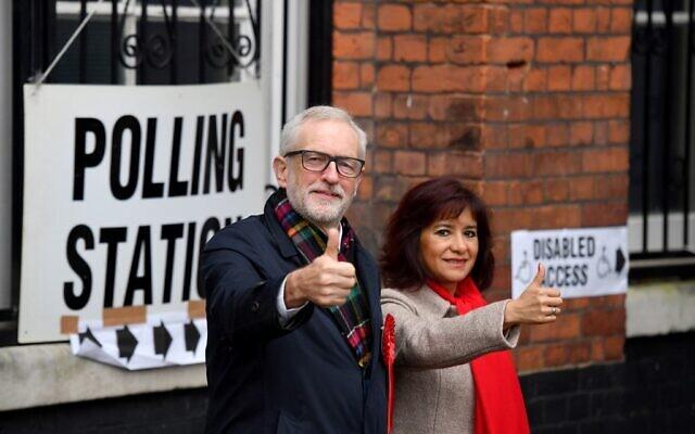 Le leader du parti Travailliste britannique Jeremy Corbyn et son épouse Laura Alvarez posent à leur arrivée à un bureau de vote dans le nord de Londres, le 12 décembre 2019, alors que la Grande-Bretagne vote pour ses élections générales (Crédit : DANIEL LEAL-OLIVAS / AFP)