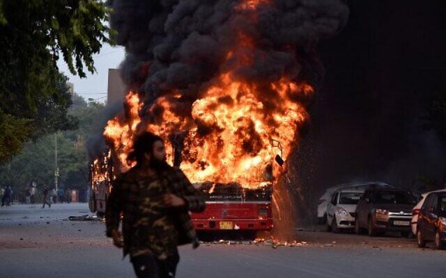 Un autobus en feu à la suite d'une manifestation contre le projet de loi du gouvernement indien sur la citoyenneté à New Delhi le 15 décembre 2019. (Crédit : STR / AFP)