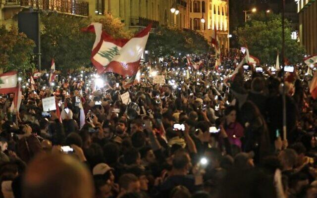 Des manifestants libanais brandissent le drapeau national pendant une manifestation anti-gouvernementale dans le centre-ville de la capitale Beyrouth, le 15 décembre 2019. (Crédit : ANWAR AMRO / AFP)