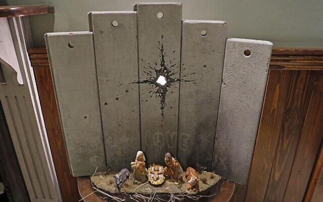 """Une nouvelle oeuvre de Noël, """"La cicatrice de Bethléem"""", réalisée par l'artiste britannique Banksy, exposée au Walled-Off Hotel à Bethléem, en Cisjordanie, le 20 décembre 2019 (Crédit :  AHMAD GHARABLI / AFP)"""