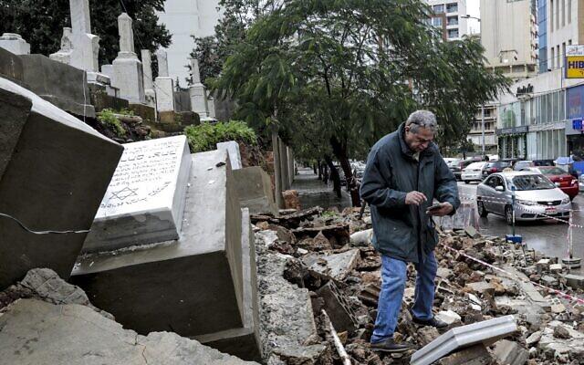 Un homme inspecte des tombes endommagées par le mauvais temps lors d'une tempête hivernale au cimetière juif de la capitale libanaise, Beyrouth, le 26 décembre 2019. (Crédit : ANWAR AMRO / AFP)