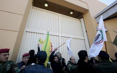 Des membres des forces de sécurité irakiennes tentent d'éloigner les manifestants d'une des portes de l'ambassade américaine après avoir franchi le mur extérieur de la mission diplomatique à Bagdad lors d'une manifestation de colère le 31 décembre 2019 pour dénoncer les frappes aériennes américaines du week-end qui ont tué des individus issus de groupes soutenus par l'Iran en Irak. (Crédit : AHMAD AL-RUBAYE / AFP)