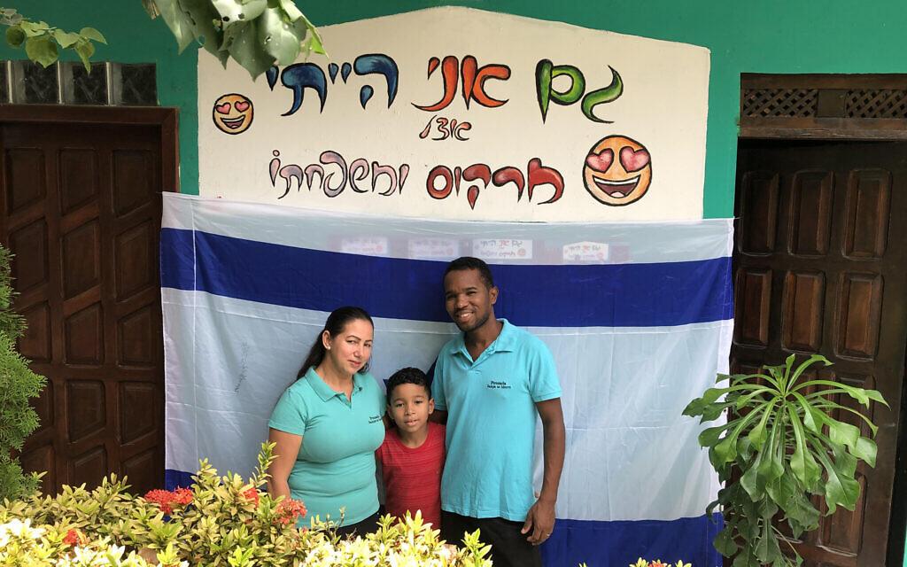 """La famille Santos pose à l'endroit où l'on peut lire sur la photo: """"J'étais aussi avec Marcos et sa famille"""", à l'hôtel Sampa no Morro. (Marcus Gilban/JTA)"""