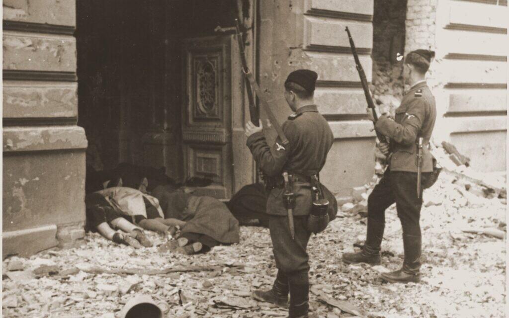 Des gardes Askari ou Trawniki regardent par une porte les corps des Juifs tués pendant la répression du soulèvement dans le ghetto de Varsovie. (Crédit : musée de la Shoah de Washington)