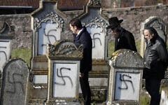 Le ministre français de l'Intérieur Christophe Castaner, au centre, suivi du rabbin en chef de Strasbourg Harold Abraham Weill, deuxième à droite, marche au milieu des tombes vandalisées dans le cimetière juif de Westhoffen, à l'ouest de la ville de Strasbourg, dans l'est de la France, le mercredi 4 décembre 2019. (Crédit : AP / Jean-François Badias)