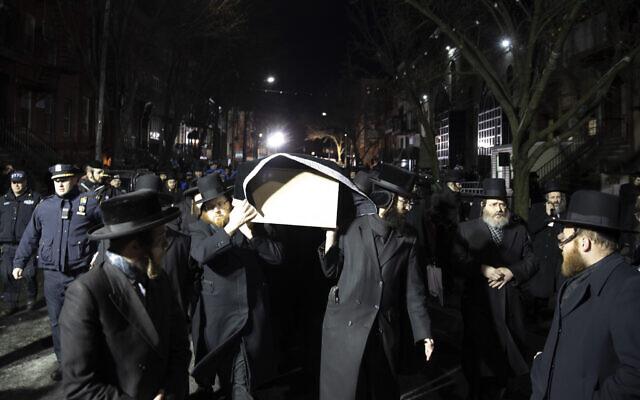 Des juifs orthodoxes portent le cercueil avec Mindel Ferencz devant une synagogue de Brooklyn, le mercredi 11 décembre 2019, à New York. Ses funérailles auront lieu à Jersey City. Ferencz a été tué mardi lors de la fusillade dans son épicerie casher de Jersey City. (Crédit : AP Photo/Mark Lennihan)