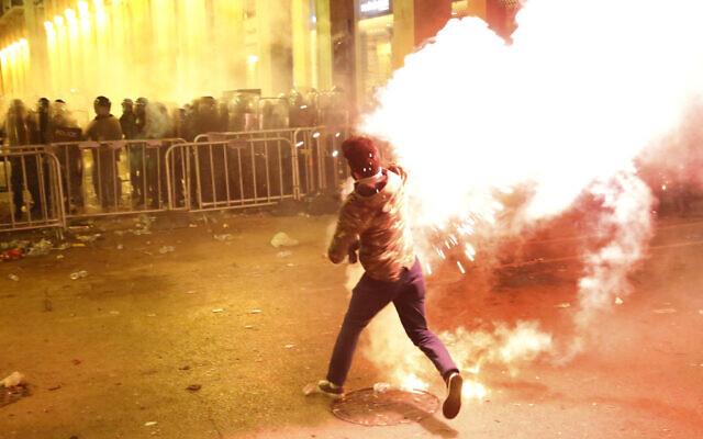 Un manifestant anti-gouvernemental lance des fusées contre la police anti-émeute, en arrière-plan, lors d'une manifestation près de la place du Parlement, au centre de Beyrouth, Liban, le 15 décembre 2019. (Crédit : AP Photo/Hussein Malla)