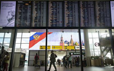 Des passagers devant un panneau de départ à l'aéroport international Sheremetyevo de Moscou, Russie, le 8 juillet 2019. (Crédit : AP/Pavel Golovkin)