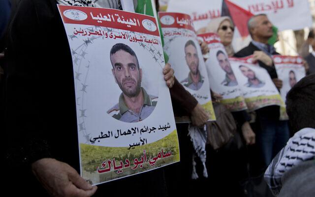 Des manifestants arborent des drapeaux palestiniens et des affiches avec des photos du terroriste Sami Abu Diak, à Ramallah, en Cisjordanie, le 26 novembre 2019. (AP Photo/Nasser Nasser)