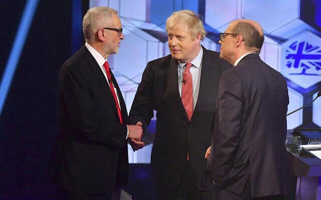 Le chef du parti travailliste de l'opposition Jeremy Corbyn, à gauche, serre la main du premier ministre britannique Boris Johnson, au centre, avec l'animateur du débat Nick Robinson, à droite, lors d'un débat en direct sur les élections aux studios de la BBC à Maidstone, Angleterre, le 6 décembre 2019 (Crédit : Jeff Overs/BBC via AP)