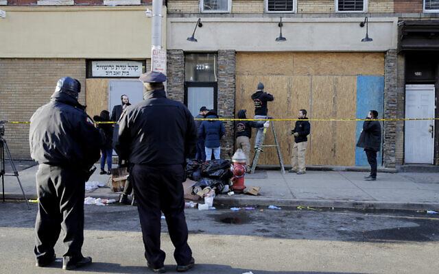 Des gens installent des planches sur la façade de l'épicerie casher qui a été le théâtre d'une fusillade à Jersey City, N.J., le mercredi 11 décembre 2019. Les deux tireurs qui se sont livrés à une féroce fusillade qui a fait plusieurs morts à Jersey City ont clairement ciblé le magasin juif, a déclaré le maire mercredi, au milieu de soupçons croissants que l'effusion de sang était une attaque antisémite. (AP Photo/Seth Wenig)