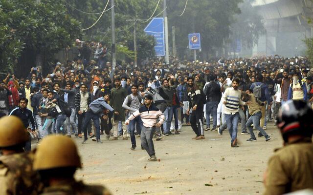 Des étudiants crient des slogans devant l'Université Jamia Millia Islamia lors d'une manifestation contre le projet de loi sur la citoyenneté, à New Delhi, Inde, le 13 décembre 2019. (Crédit : AP Photo)