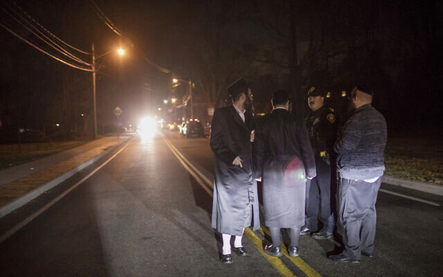 Des Juifs orthodoxes sur Forshay Road à Monsey, N.Y., en bas de la rue où s'est produite une attaque au couteau arrivée samedi soir pendant une célébrationd e Hanoukka (Crédit :  AP/Allyse Pulliam)