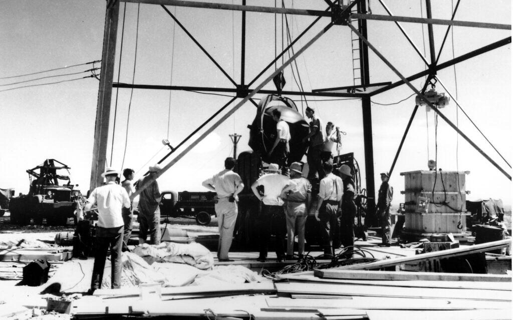 Des scientifiques et des ouvriers construisent la première bombe atomique au monde qui est montée dans une tour de 30 mètres de haut à Trinity, le site d'essai de la bombe, dans le désert près d'Alamagordo, au Nouveau-Mexique, en juillet 1945. (AP Photo)