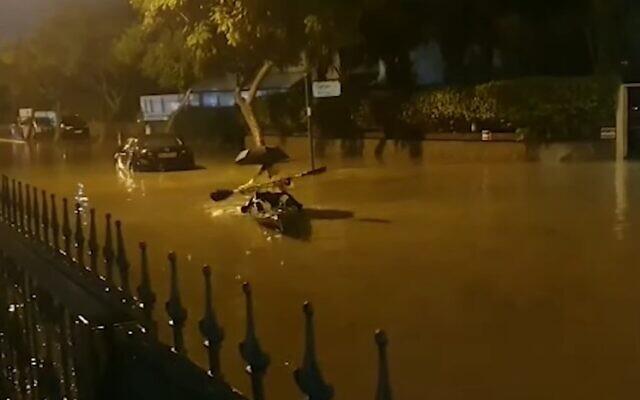 Des gens pagaient sur une route inondée dans la ville d'Ashkelon, dans le sud d'Israël, le  12 décembre 2019 (Capture d'écran YouTube)