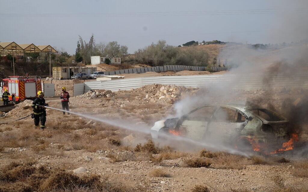 Des pompiers éteignent un incendie dans une voiture lors d'un exercice de l'armée israélienne simulant une attaque à la roquette dans l'implantation de Kfar Adumim, en Cisjordanie, le 11 décembre 2019. (Crédit ; Judah Ari Gross/The Times of Israel)