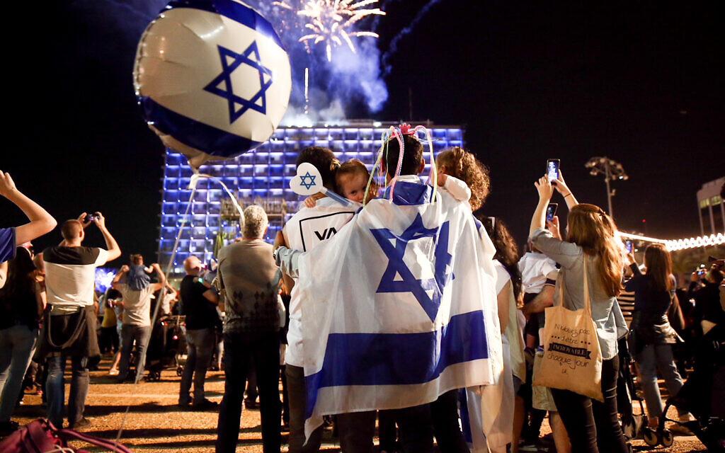 Des Israéliens devant des feux d'artifice à la mairie de Tel Aviv, le 18 avril 2018, à l'occasion du 70e jour de l'indépendance d'Israël. (Crédit : Miriam Alster / Flash90)