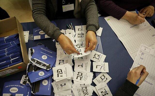 Des agents dépouillent les bulletins de vote des soldats et des votes par correspondance à la Knesset à Jérusalem, un jour après les élections générales, le 10 avril 2019. (Noam Revkin Fenton/Flash90)