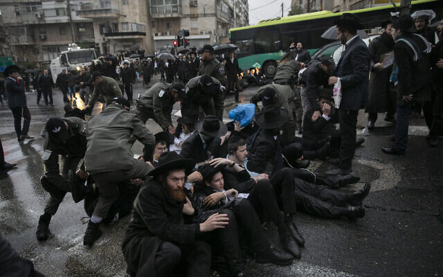Des ultra-orthodoxes bloquent une route lors d'une manifestation contre l'emprisonnement d'un étudiant de yeshiva qui n'a pas respecté un ordre de recrutement militaire, Jérusalem, le 8 décembre 2019. (Crédit : Olivier Fitoussi/Flash90)